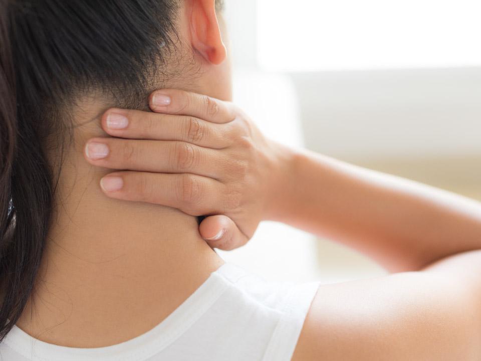 首の痛みに悩む女性の画像
